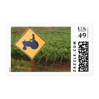 A yellow tractor crossing sign in the vineyard postage