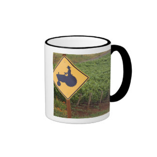 A yellow tractor crossing sign in the vineyard ringer mug