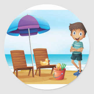 A young boy at the beach near the wooden chairs round sticker