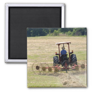 A young boy driving a tractor harvesting magnet