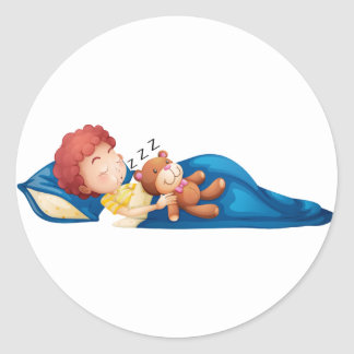 A young boy sleeping round stickers