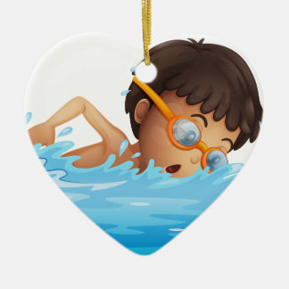 A young boy swimming with a yellow goggles ceramic ornament