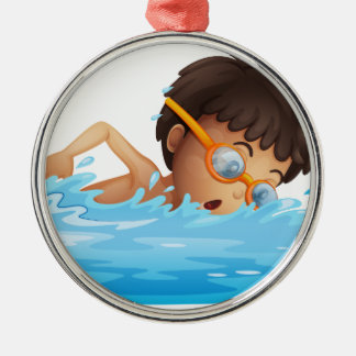 A young boy swimming with a yellow goggles metal ornament