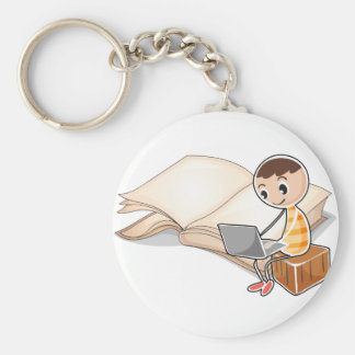 A young boy with a laptop near the big book basic round button keychain