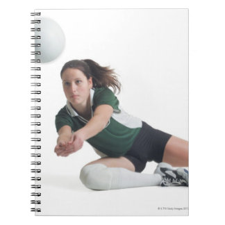 a young caucasian female volleyball player in a notebook