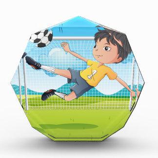 A young gentleman kicking a soccer ball award