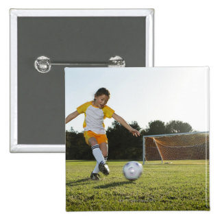 A young girl playing soccer on a soccer field in button