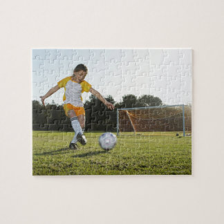 A young girl playing soccer on a soccer field in jigsaw puzzle