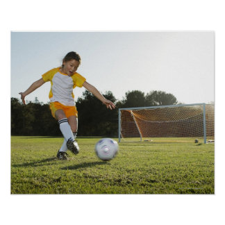 A young girl playing soccer on a soccer field in poster