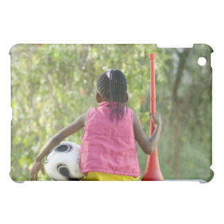 A young girl sits on a bench, holding a Vuvuzela iPad Mini Cover