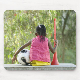 A young girl sits on a bench, holding a Vuvuzela Mouse Pad
