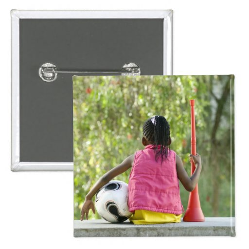 A young girl sits on a bench, holding a Vuvuzela Pinback Button