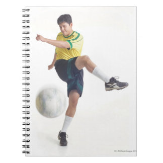 a young latin male wears a yellow soccer jersey notebook