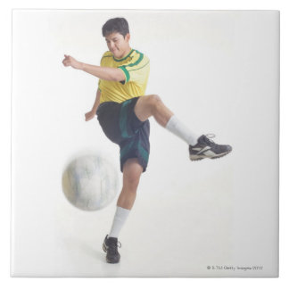 a young latin male wears a yellow soccer jersey tile