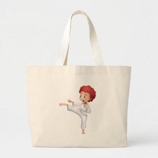 A young man doing karate tote bag