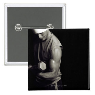 A young man lifts weights. 2 inch square button