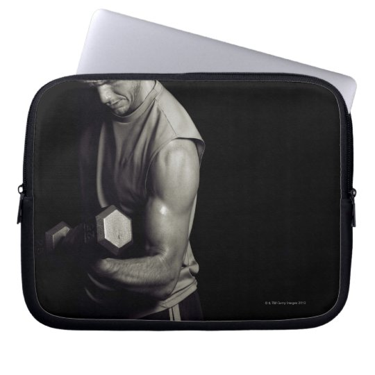 A young man lifts weights. computer sleeve