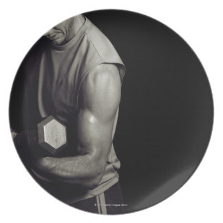 A young man lifts weights. dinner plates