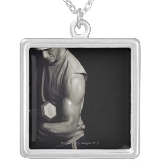 A young man lifts weights. square pendant necklace