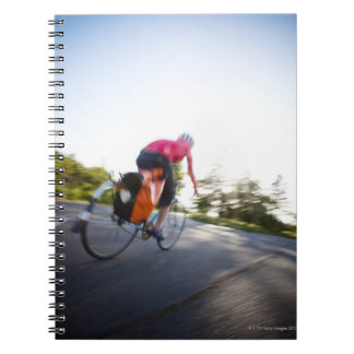 A young woman rides a bike around a park at notebook