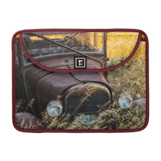 Abandoned old car in tall grass MacBook pro sleeve