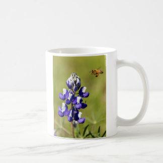 Abeja ocupada que comtempla una flor salvaje del taza clásica