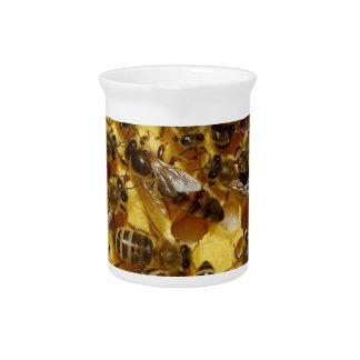 Abejas de la miel en colmena con la reina en centr jarras de beber
