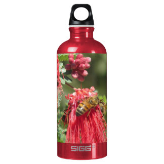 Abejas en la botella rosada de la flor