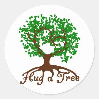 Abrace a un pegatina redondo del árbol