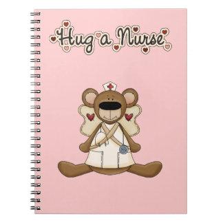 Abrace a una enfermera libros de apuntes con espiral