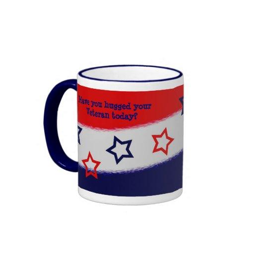 Abrace una taza blanca del veterano y azul roja