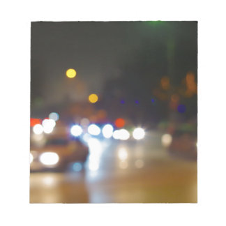 Abstract blurry spots of light in the night city notepad