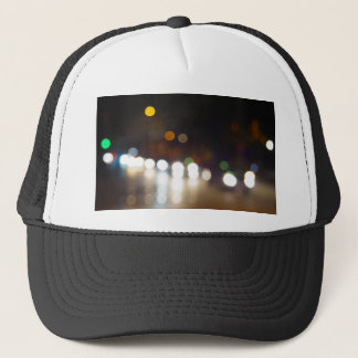 Abstract blurry spots of light in the night city s trucker hat