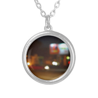 Abstract night scene with dim lights and headlight round pendant necklace