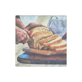 Abuela que corta el pan imán de piedra