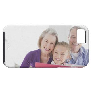 Abuelos sonrientes que leen el libro de cocina con iPhone 5 cobertura