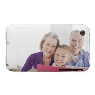Abuelos sonrientes que leen el libro de cocina con iPhone 3 cobreturas