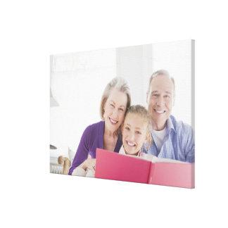 Abuelos sonrientes que leen el libro de cocina con impresiones de lienzo