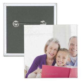 Abuelos sonrientes que leen el libro de cocina con pin cuadrada 5 cm