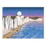 Acantilados de la puesta del sol por el océano tarjeta postal