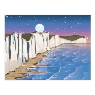 Acantilados de la puesta del sol por el océano postal