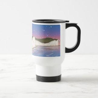 Acantilados de la puesta del sol por el océano taza térmica