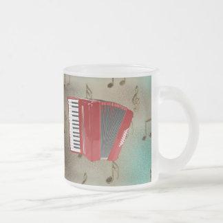 Acordeón rojo en notas musicales tazas