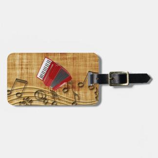 Acordeón rojo, notas negras, fondo del oro etiquetas bolsa