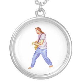 acoustic guitar player jeans feet apart round pendant necklace