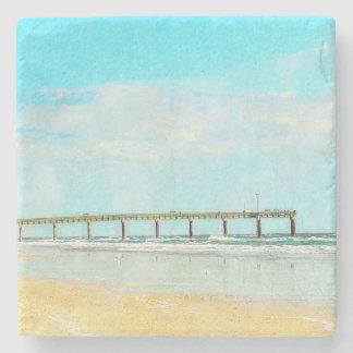 Acuarela de la playa del océano y del embarcadero posavasos de piedra