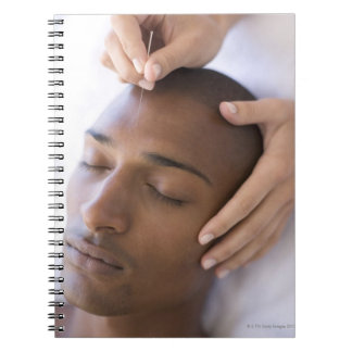 Acupuncture. Acupuncturist inserting a needle Spiral Notebook