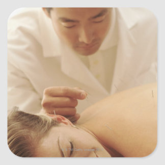 Acupuncturist putting needles in woman's back square sticker