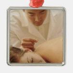 Acupuncturist que pone agujas en la mujer detrás adorno