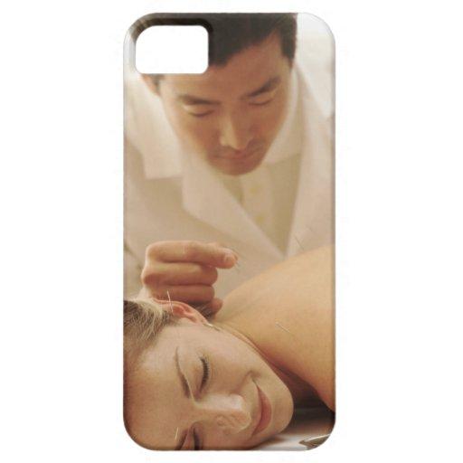 Acupuncturist que pone agujas en la mujer detrás iPhone 5 protectores